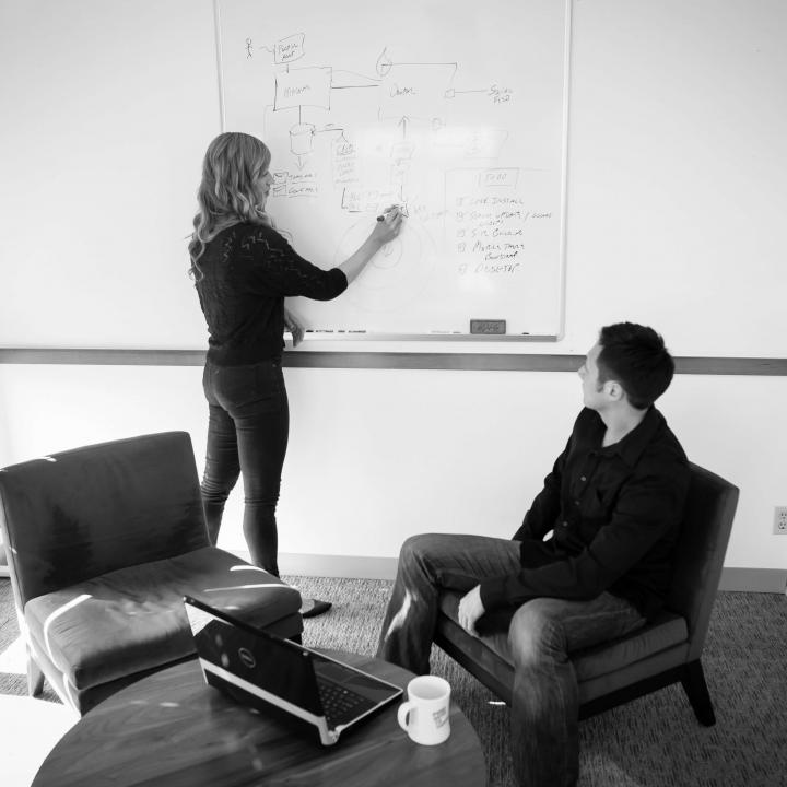a woman and a man discuss topics on a whiteboard